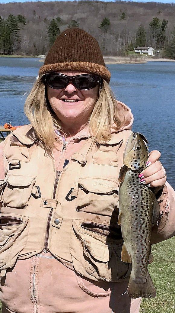 Carol smiles big after landing a nice brown trout at