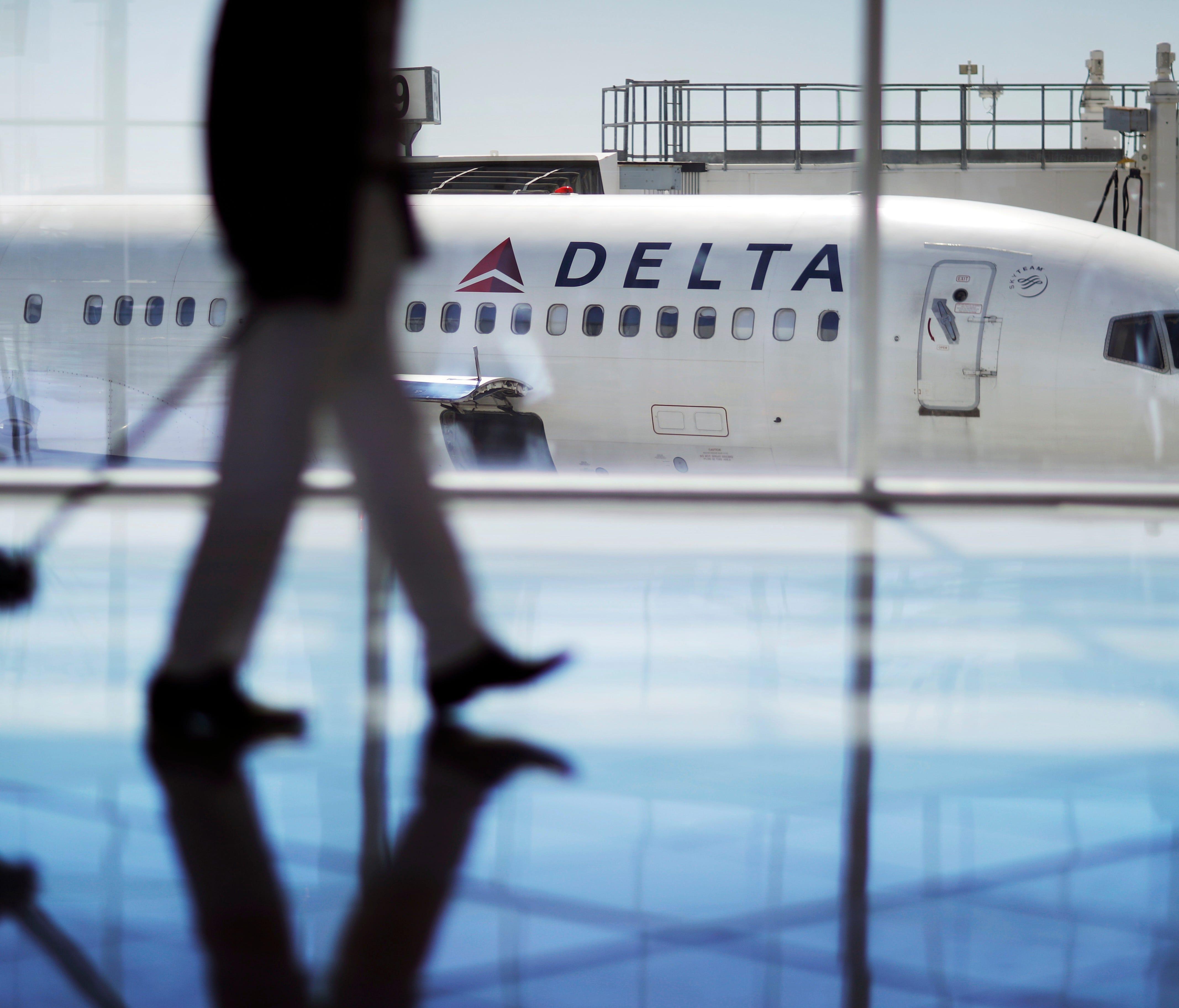 A man walks past a Delta Air Lines jet Oct. 13, 2016, at Hartsfield-Jackson Atlanta International Airport in Atlanta.