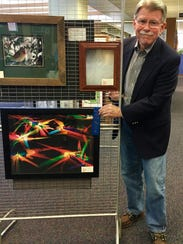 """Tom Farris stands next to his winning photograph """"Symphonic"""