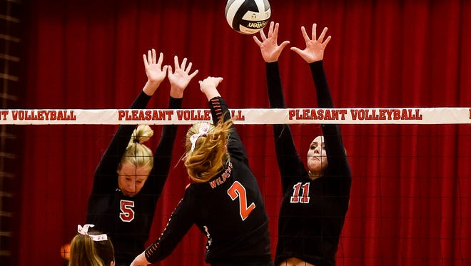 Pleasant High School's Summer Blevins and Lydia DePrey block a spike from North Union's Katie Dotson during the Pleasant vs North Union Volleyball game on tuesday night.