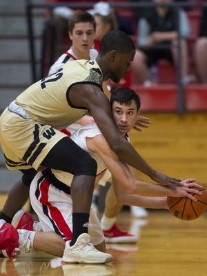 Center Grove High School junior Ben Nicoson (1) looks for help from his teammates as he is defended by Warren Central High School junior David Bell (22) after picking up a loose ball during the first half of an IHSAA boys' varsity basketball game Thursday, February 1, 2018, at Center Grove High School.
