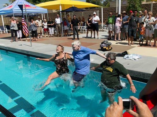 John Furbee, center, joins in the inaugural swim at