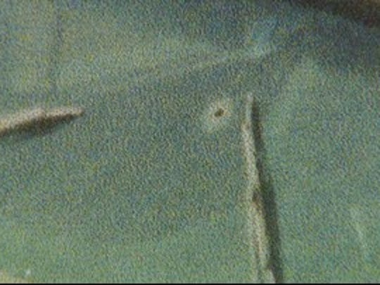 This is a closeup image of what Bob Lucas believes was a bullet hole through the windshield of the 1960 Lincoln convertible he purchased from a farmer in East Jordan, Mi. in 1990. To this day, Lucas believes somebody was killed inside the car.