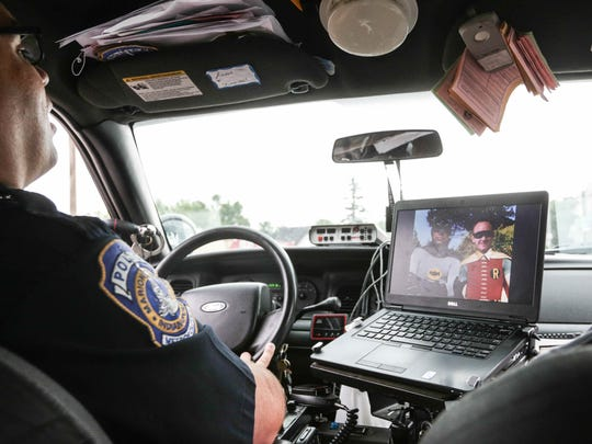 IMPD patrolman Adam Perkins, left, and CORE paramedic Shane Hardwick, right, patrol the east side with a Photoshopped  picture of the tandem as Batman and Robin on their computer's screensaver.