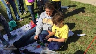 Southern Miss student Lindsey Calhoun and Sacred Heart fourth grader Brian Nicholson make a God's Eye at Native American Ways day.