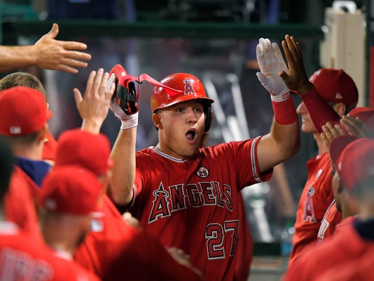 Los Angeles Angels' Mike Trout is congratulated by teammates after scoring on a double by Kole Calhoun during the first inning of a baseball game against the Houston Astros, Wednesday, Sept. 13, 2017, in Anaheim, Calif. (AP Photo/Mark J. Terrill)