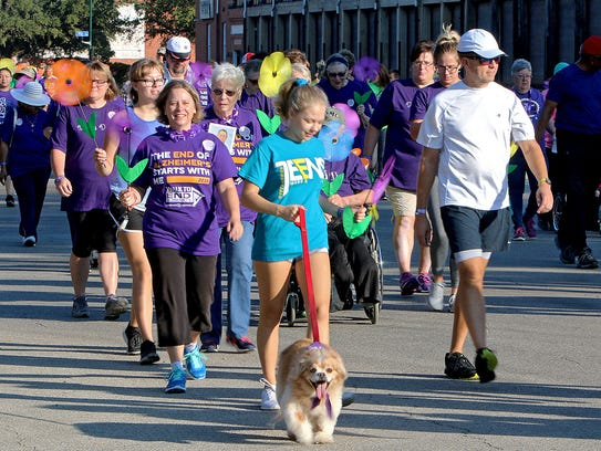 A group, including a dog, walks down Ohio Avenue carrying