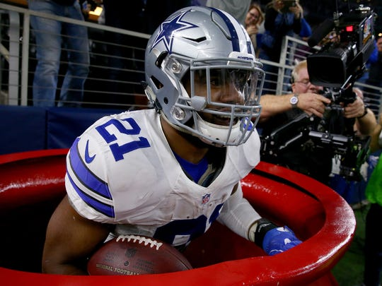 Cowboys RB Ezekiel Elliott celebrates after scoring by jumping into a Salvation Army red kettle during the second quarter against the Tampa Bay Buccaneers at AT&T Stadium on Dec.18, 2016.