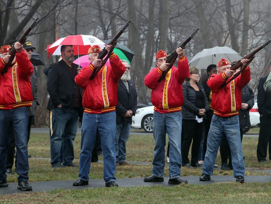 An honor guard fires rifles during a burial ceremony