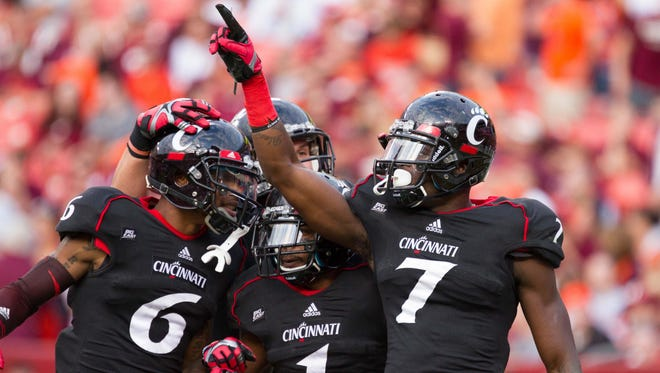 Cincinnati Bearcats wide receiver Kenbrell Thompkins (7) celebrates with teammates wide receiver Anthony McClung (6) and running back Ralph David Abernathy (1) after scoring a touchdown against the Virginia Tech Hokies during the third quarter at FedEx Field.