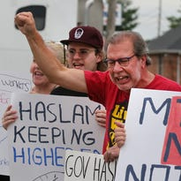 Scott Martindale holds up a sign with others protesting against Governor Bill Haslam, in front of a Pilot gas station on Church Street in Murfreesboro Tuesday, Aug. 23, 2016