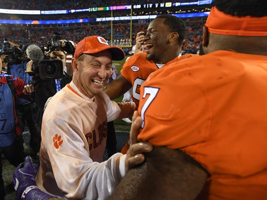 Clemson head coach Dabo Swinney celebrates with defensive lineman Clelin Ferrell (99), center, and defensive lineman Austin Bryant (7) after the Tigers 38-3 win over Miami in the ACC championship at Bank of America Stadium in Charlotte on Saturday, December 2, 2017.