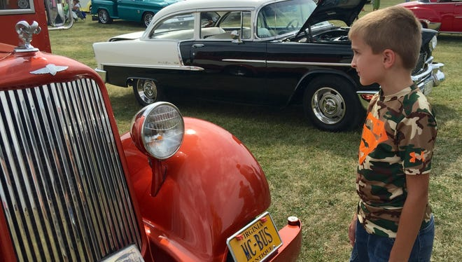 Hayden Glendye, 8, looks at a restored bus at the Big Truck & Auto Show in Fishersville.