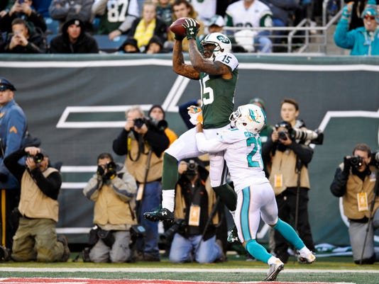 New York Jets' Brandon Marshall (15) catches a pass in front of Miami Dolphins' Brent Grimes (21) for a touchdown during the second half of an NFL football game Sunday, Nov. 29, 2015, in East Rutherford, N.J. (AP Photo/Bill Kostroun)
