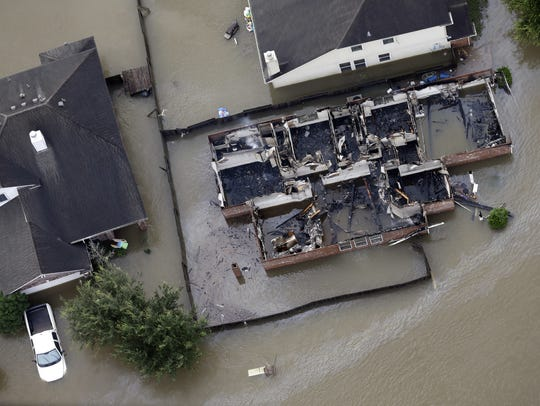 A burned out home is surrounded by floodwaters from