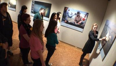 "Catie Anderson, a curator of education at the Woodson Art Museum, explains to D.C. Everest Junior High School art students some of the compositional elements of a piece in the exhibition ""50 Greatest National Geographic Photographs"" in December 2014."