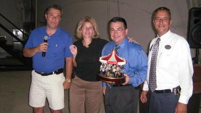 Kimberle Rolle Samarelli,  second from left, is shown in this 2007 photo with, left to right, Paul Levchuk of the New Jersey Amusement Association, and Mark Kane and Ed Zakar of Six Flags Great Adventure. Rolle Samarelli, executive director of the New Jersey Amusement Association, is charged with stealing from the Pelican Island Property Owners Association, where she lives.