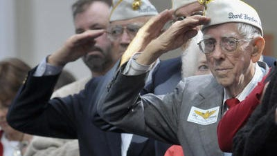 Jay Carraway, right, salutes at a Pearl Harbor ceremony in 2009.