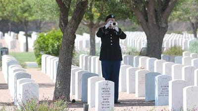 A soldier plays taps off in the distance for Navy World War II veteran Albert A. Portugal at the Fort Bliss National Cemetery in April.
