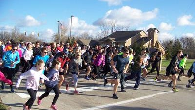 An enthusiastic crowd of runners leaves the starting line at the 2015 Turkey Trot, sponsored by the Livonia Parks & Recreation Department, in this file photo.