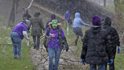 Volunteers from FedEx work with Keep Indianapolis Beautiful on a project along Fall Creek on April 16.
