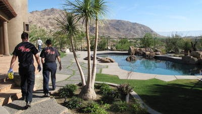 Cal Fire personnel walk by a pool at a home under construction in the 71-300 block of Cholla Way near Palm Desert on June 2, 2010, after an explosion that injured a pool company employee. Victor Regalado of Thermal suffered third-degree burns while testing a propane line in an underground vault and was airlifted to the Arrowhead Regional Medical Center burn unit in Colton.