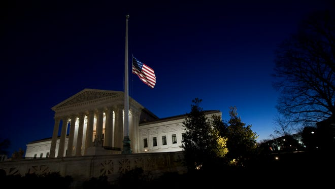 An American flag flies at half-staff in front of the U.S. Supreme Court building in Washington, as the sun rises Sunday, Feb. 14, 2016, in honor of Supreme Court Justice Antonin Scalia. Scalia, the influential conservative and most provocative member of the Supreme Court, has died. He was 79.