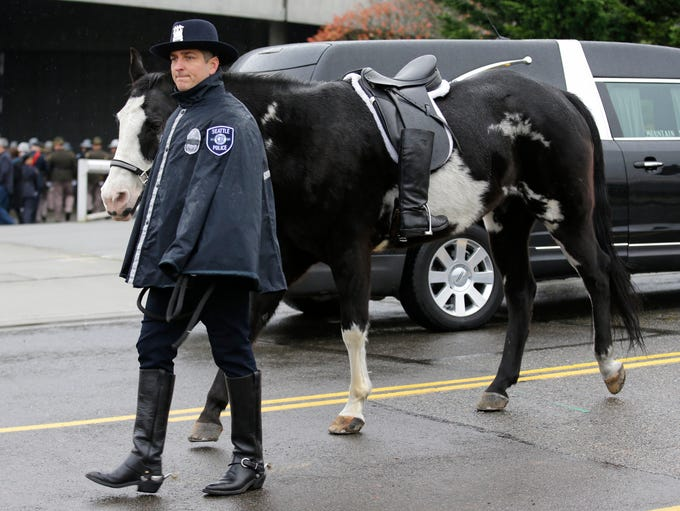 A Seattle Police officer leads a riderless horse with