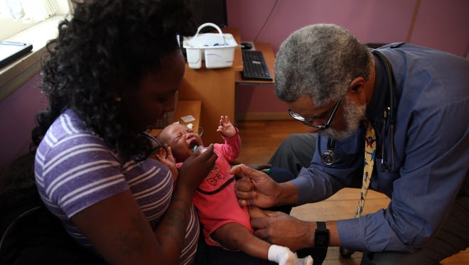 Dr. Wendell Wheeler gives vaccinations to Ny-riel Wilson, as her mother Briana Steele, holds her on Feb. 3 in South Holland, Illinois. Ny-riel Wilson was not vaccinated for measles during this visit because she is too young for that vaccination.