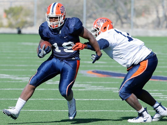 UTEP running back Treyvon Hughes manages to escape the grasp of defensive lineman Denzel Chukwukelu during the team's practice in April at Glory Field.