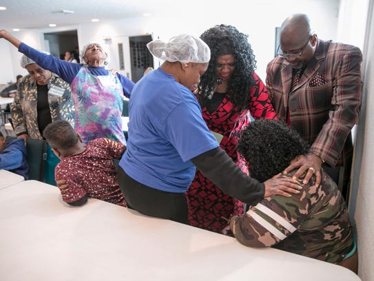 Parishioners pray for a church member in the dining