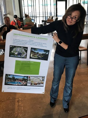 Allison Tant, chair of Independence Landing Inc., shows poster used in talks about community she wants to build for people with developmental disabilities. The photos in this poster show The Villages at Noah's Ark Lakeland.