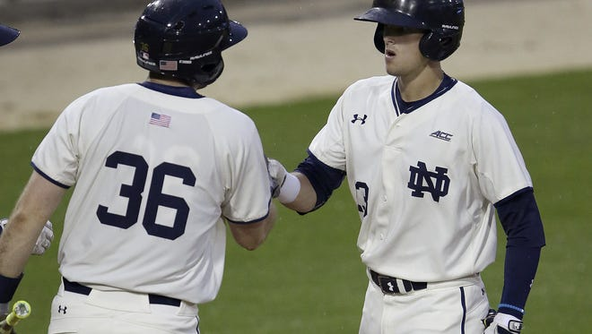 Notre Dame infielder Cavan Biggio right, is congratulated by Ryan Lidge (36) after hitting a home run in the bottom of the 3rd inning of their game Tuesday, April 26, 2016, evening at Victory Field in Indianapolis. On Friday, Biggio was drafted by the Toronton Blue Jays.