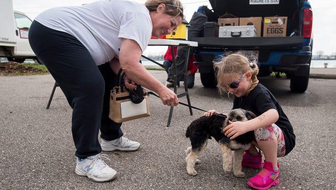Carol Hanba, left, watches as Carmen Anders, 4, pets Steve, Hanba's 2-year-old Yorkie-Poo at the Knights of Columbus Farmers Market Friday, May 4 at Marysville City Park.