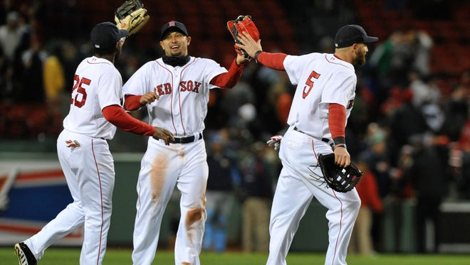 Boston Red Sox center fielder Jackie Bradley Jr., left, right fielder Shane Victorino, center, and left fielder Jonny Gomes celebrate their victory over the Tampa Bay Rays at Fenway Park.