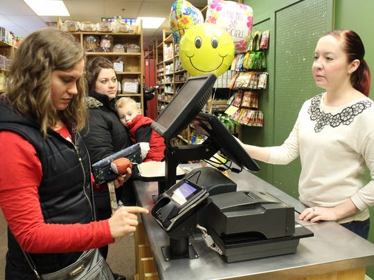 A customer checks out Friday afternoon at Downtown Grocery's temporary market in the Wausau Center mall. The new location opened Jan. 29 at 10 a.m.