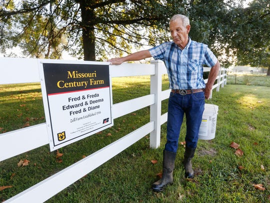 Fred Zell stands next to his century farm sign at his dairy farm in Billings.