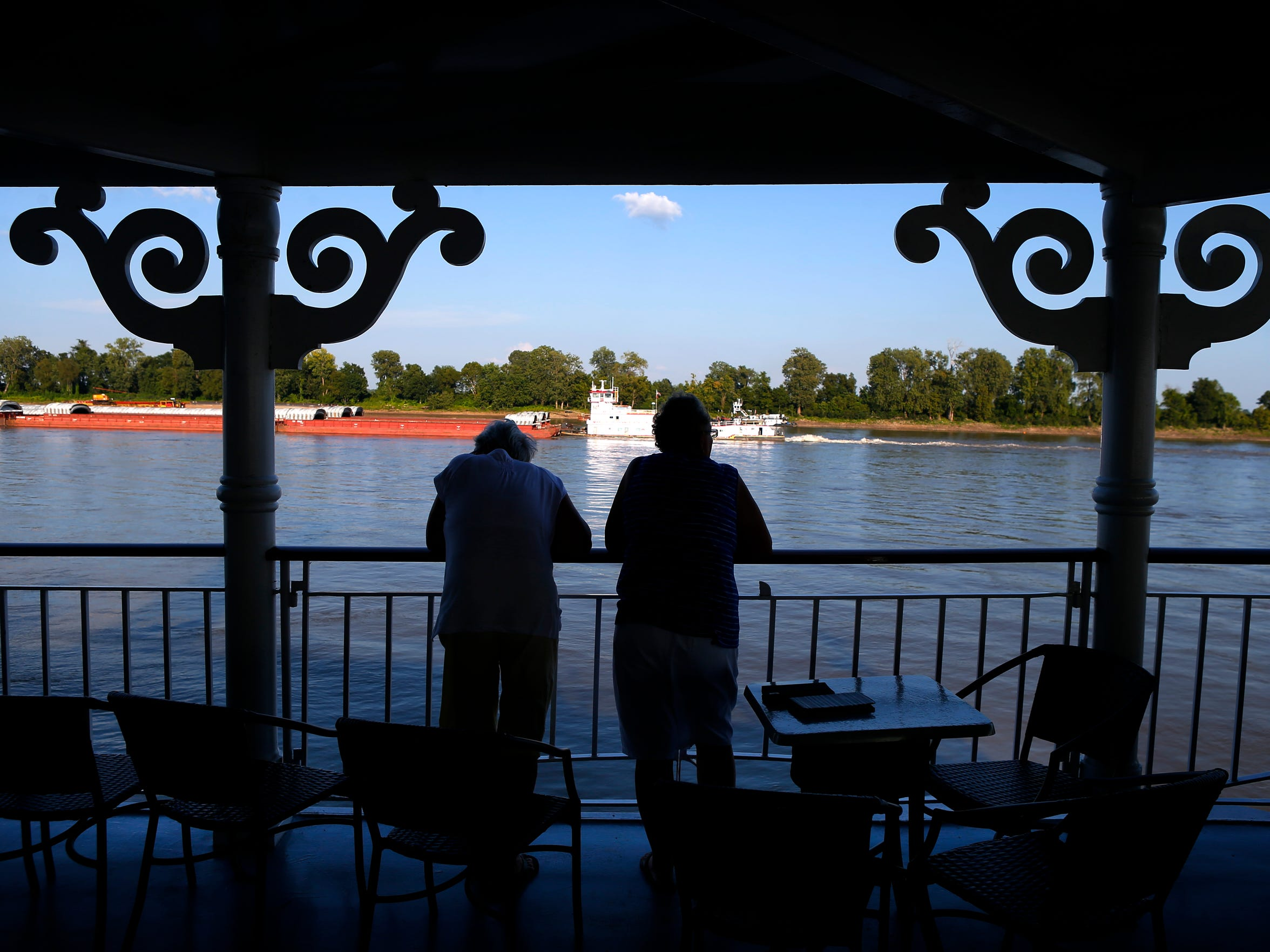 Sandy Kurtz, left, and Mary White, both of Syracuse, N.Y., gaze off the side of the American Queen steamboat on the Mississippi River.