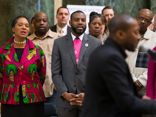 State Sen. Lena Taylor (left, D- Milwaukee) and State Rep. David Bowen (D-Milwaukee) sing along with Chris Crain during a Black History Month observance recognizing the winners of a Martin Luther King Jr. writing and speech contest at the Capitol in Madison.