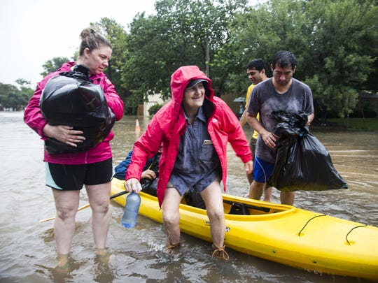 Residents of a Houston neighborhood use personal kayaks to rescue people and pets stranded by Hurricane Harvey on Aug. 29, 2017.