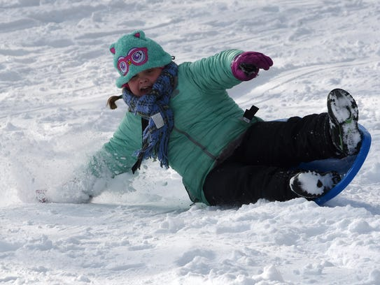 Addy Mathis bails at the bottom of the hill while sledding