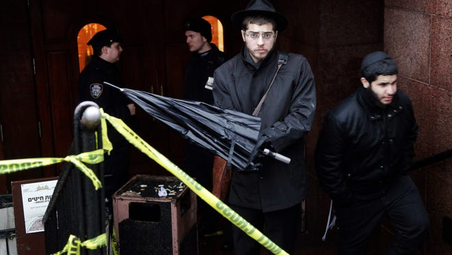 A member of the Lubavitch community, center, leaves the Chabad-Lubavitch Hasidic headquarters on Dec. 9 in New York. A knife-wielding man stabbed an Israeli student inside the Brooklyn synagogue before being fatally shot by police after he refused to drop the knife.
