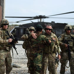 U.S. and Afghan military personnel greet each other at a coalition base in the eastern province of Nangarhar in August 2015.