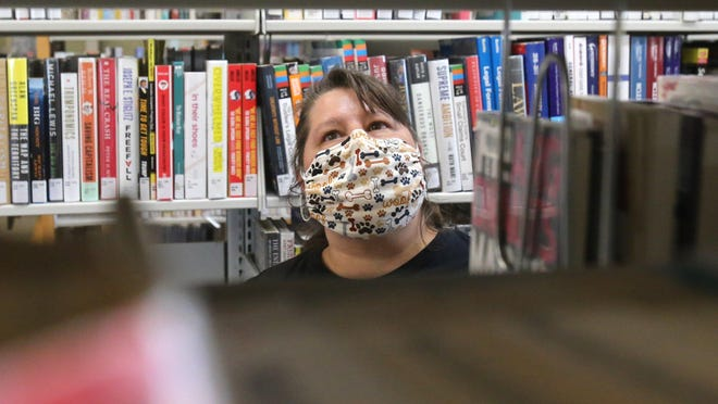 Michelle Eklich wears a mask while looking for a book at the Stark County District Library's Lake Branch on Wednesday. Governor Mike DeWine issued a statewide mask mandate that takes effect at 6 p.m. Thursday.