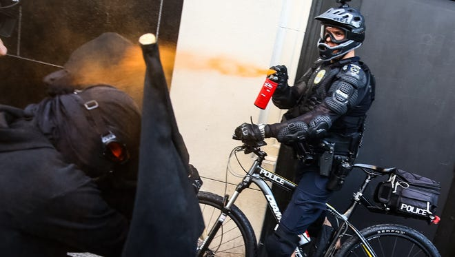 A Seattle police officer uses pepper spray during an anti-capitalism protest May 1, 2016, in Seattle. (Genna Martin/seattlepi.com via AP)