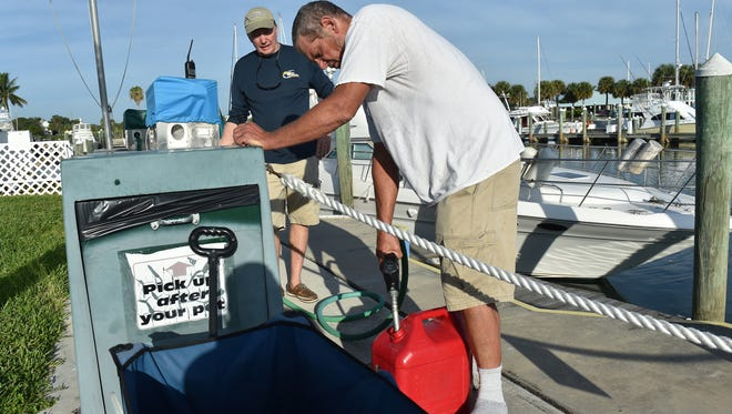 """Fort Pierce City Marina Manager Dean Kubitschek (left) assists boater Paul Morgan at the fuel dock of the marina on Wednesday, Sept. 6, 2017, in Fort Pierce as boaters secure their vessels or prepare to leave to escape Hurricane Irma. """"I'm getting out of here for safety's sake,"""" Morgan said."""