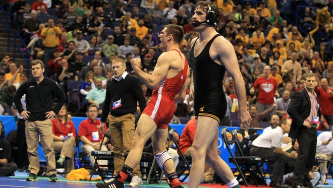 Iowa's Mike Evans walks off the mat after a 6-4 overtime loss to Nebraska's Robert Kokesh. At left are Iowa coaches Tom Brands and Ryan Morningstar; at right is Ohio State coach Tom Ryan, whose Buckeyes clinched their first team championship Saturday morning.