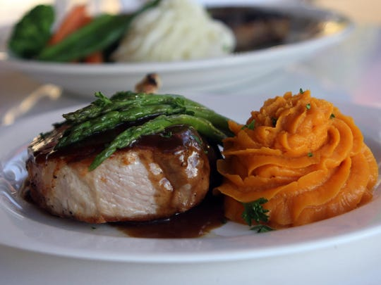The popular 10 oz pork rib chop is with blackberry demi sauce, asparagus and sweet potato mash.