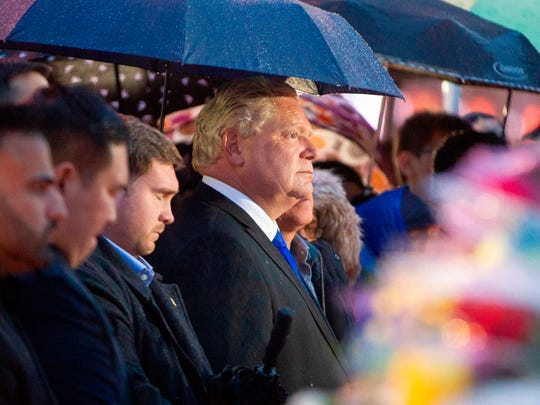 Ontario Premier Doug Ford listens during a candlelight vigil in April 2018 in Toronto, before he was elected, near the site where a van driver ran over 10 people on a sidewalk.