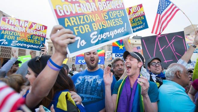 Protesters, including Christopher Bullock (center), celebrate then-Arizona Gov. Jan Brewer's announcement that she would veto last year's controversial Senate Bill 1062.